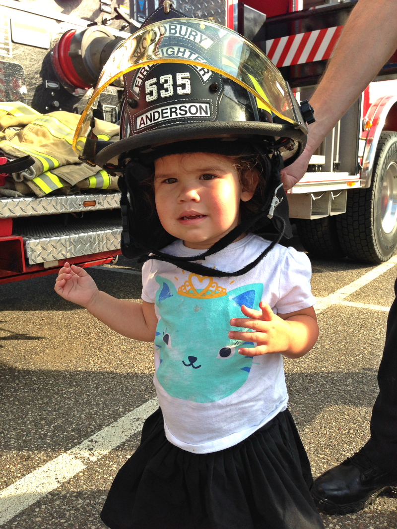 She generally hates wearing hats, but gladly put on the HEAVY fireman's helmet.